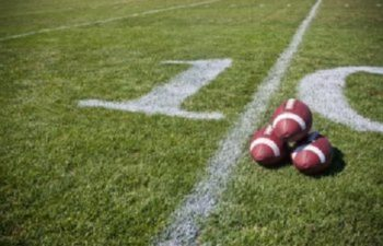 Footballs Laying on a Football Field at the 10 Yard Line